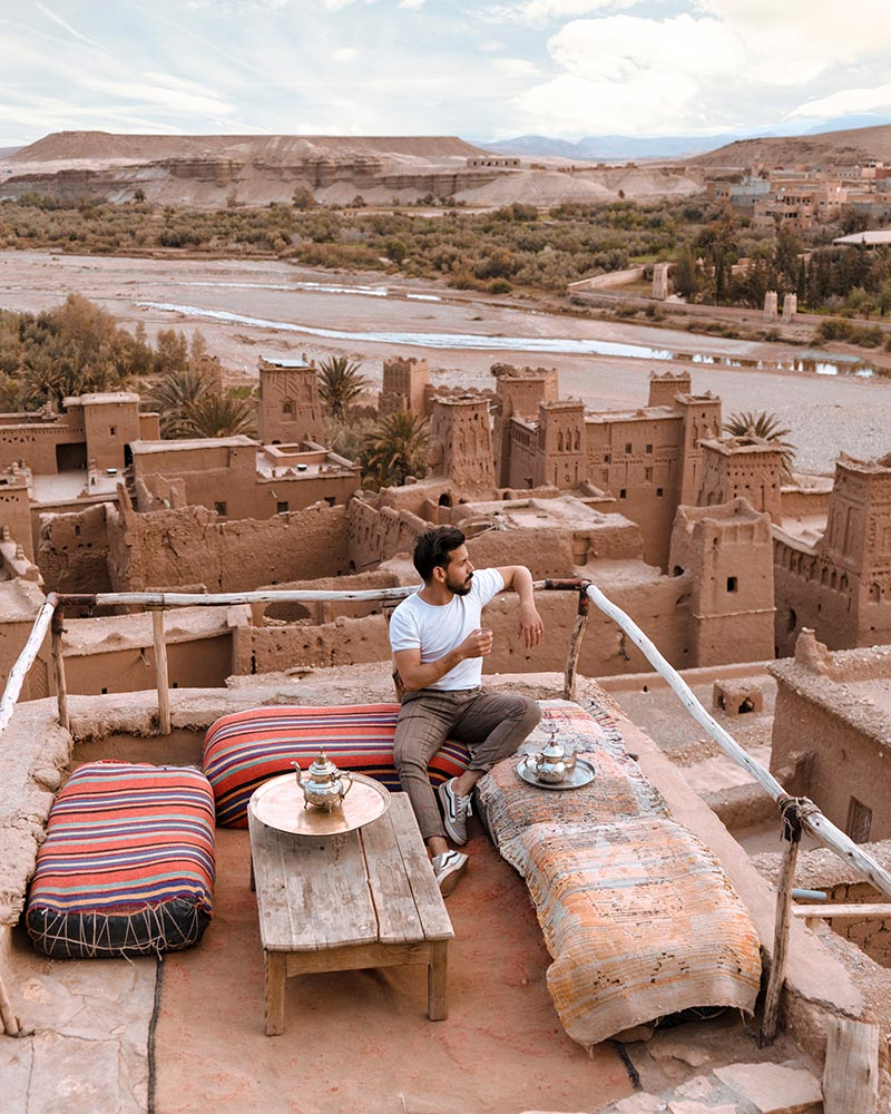 Man sitting on a roof top in the middle east looking out over a village.