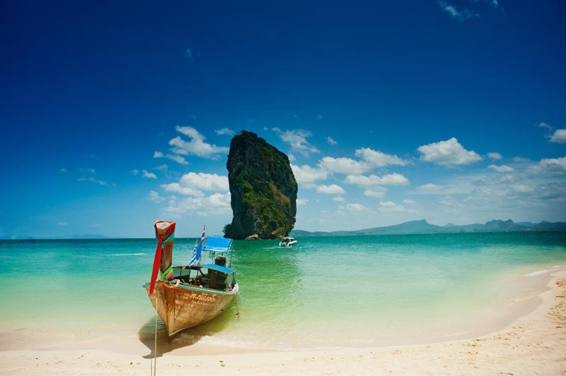 Boat on the beach in the South Pacific with beautiful sea green water.