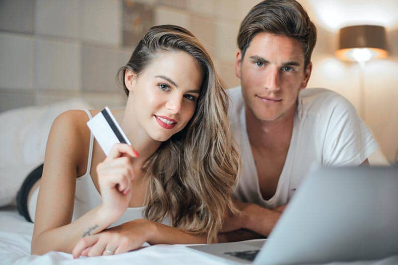 Man and woman nomads using online banking services in a hotel.