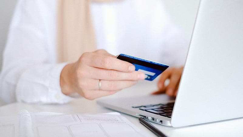 A traveler using her debit card on a computer from abroad.