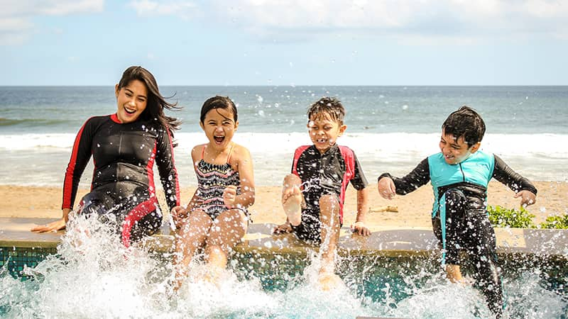 Kids playing together on the beach in a pool.