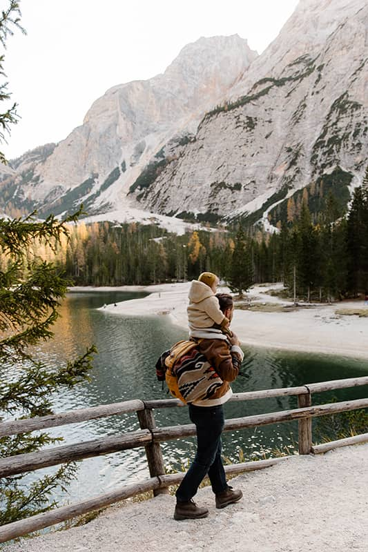Man carrying his baby on his shoulders in front of mountains as they travel together.