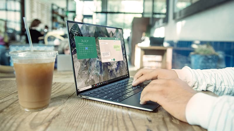 A digital nomad working remotely using a Dell XPS 13 in a coffee shop.