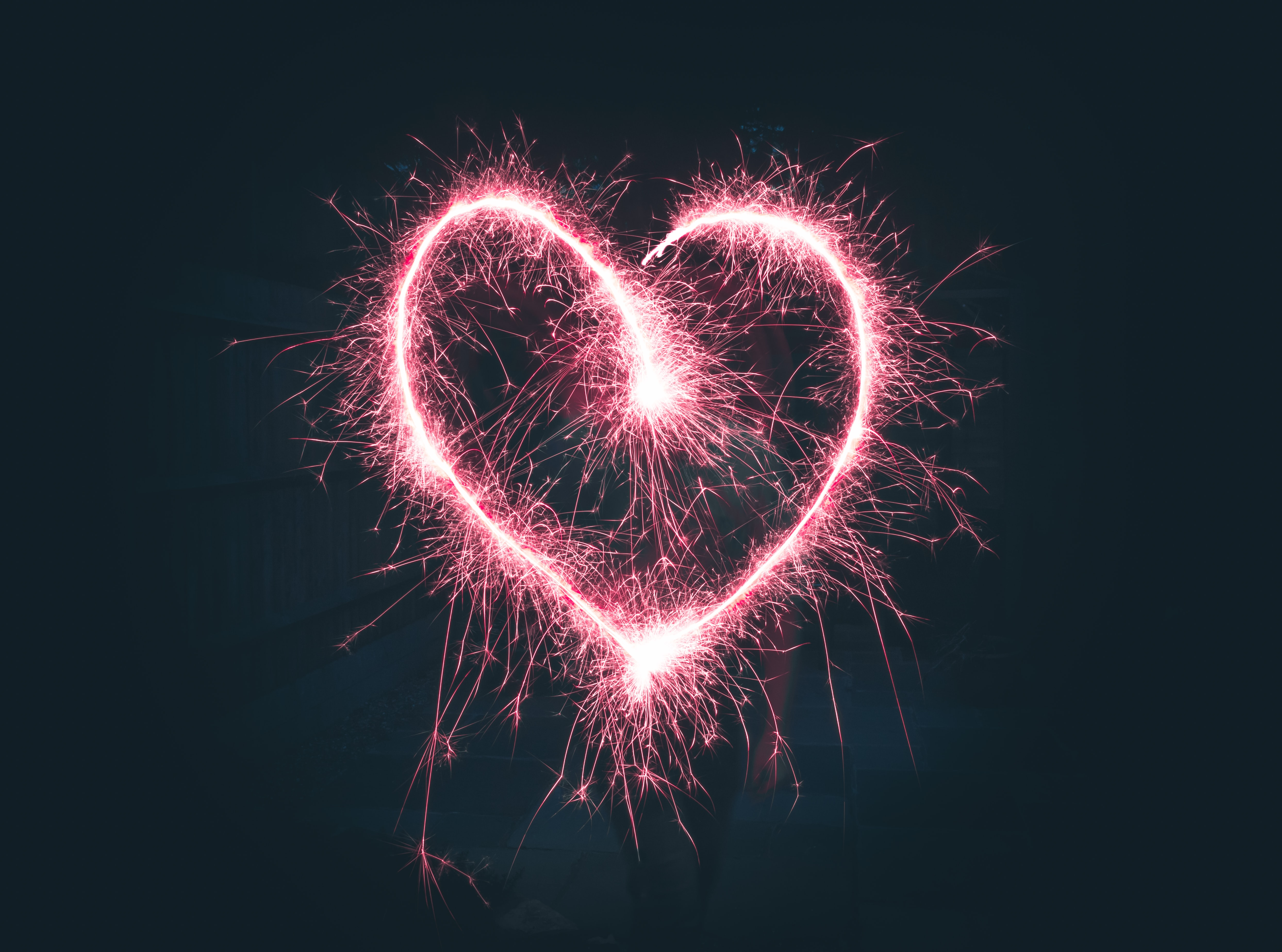 The shape of a heart made from a bright purple sparkler