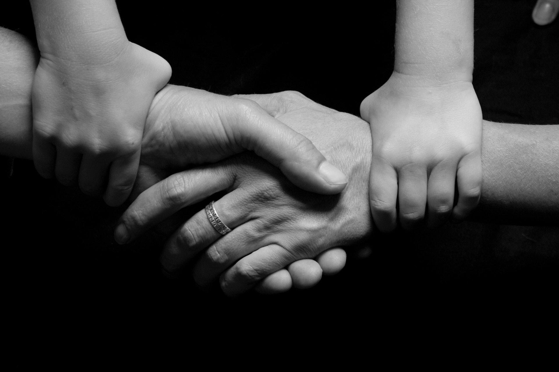 Three pairs of hands interlocked in a handshake