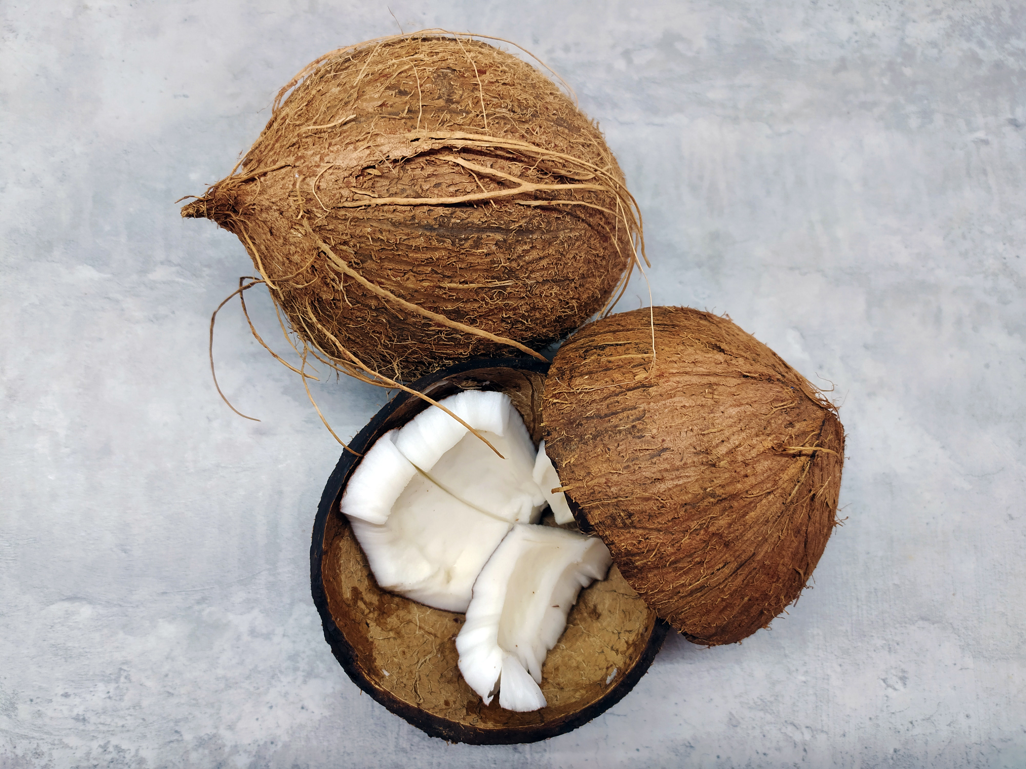 Two coconuts on a white background, one split in two