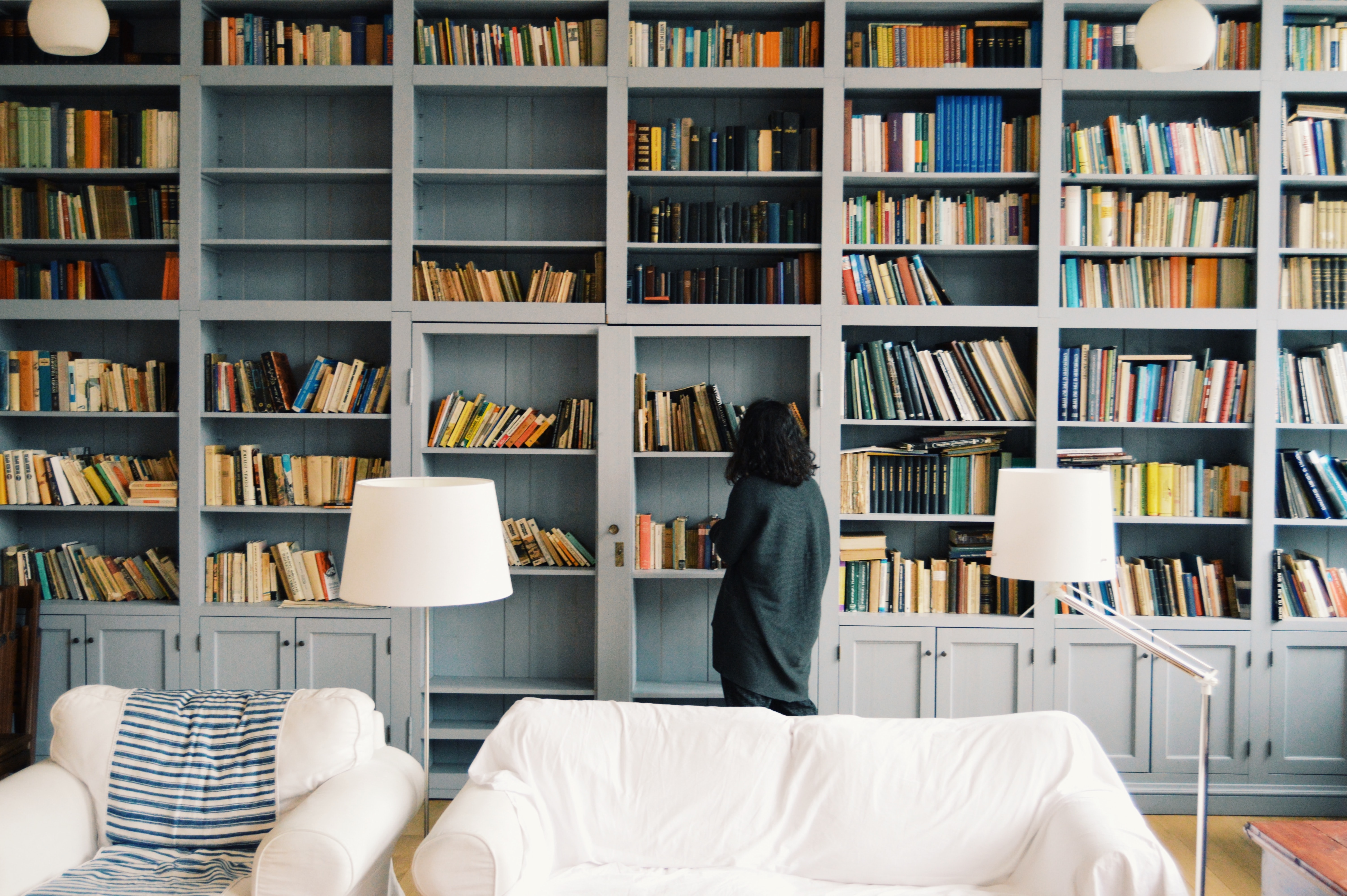 Woman looking at bookcase full of books