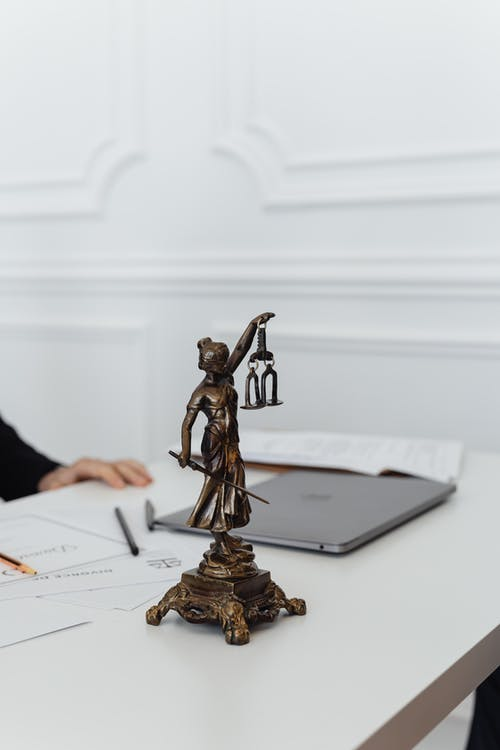 Figurine of a figure holding balancing scales on a tabletop