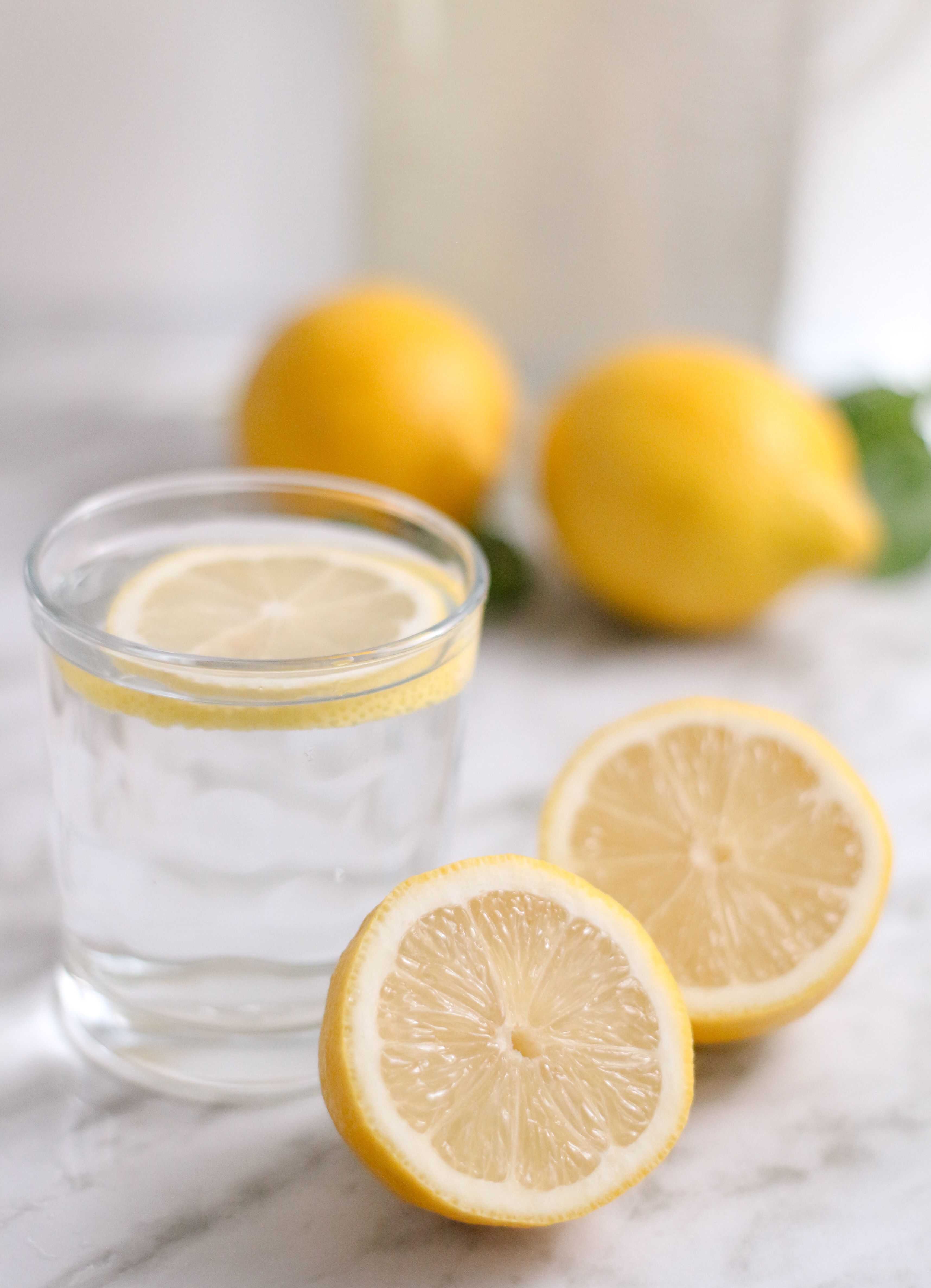 Fresh cut lemons and a glass of water with a lemon slice