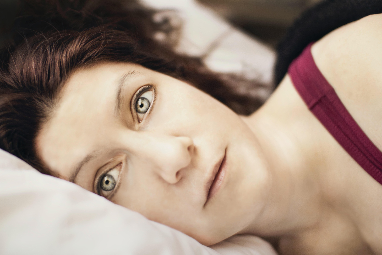 Women looking worried lying on her side in bed