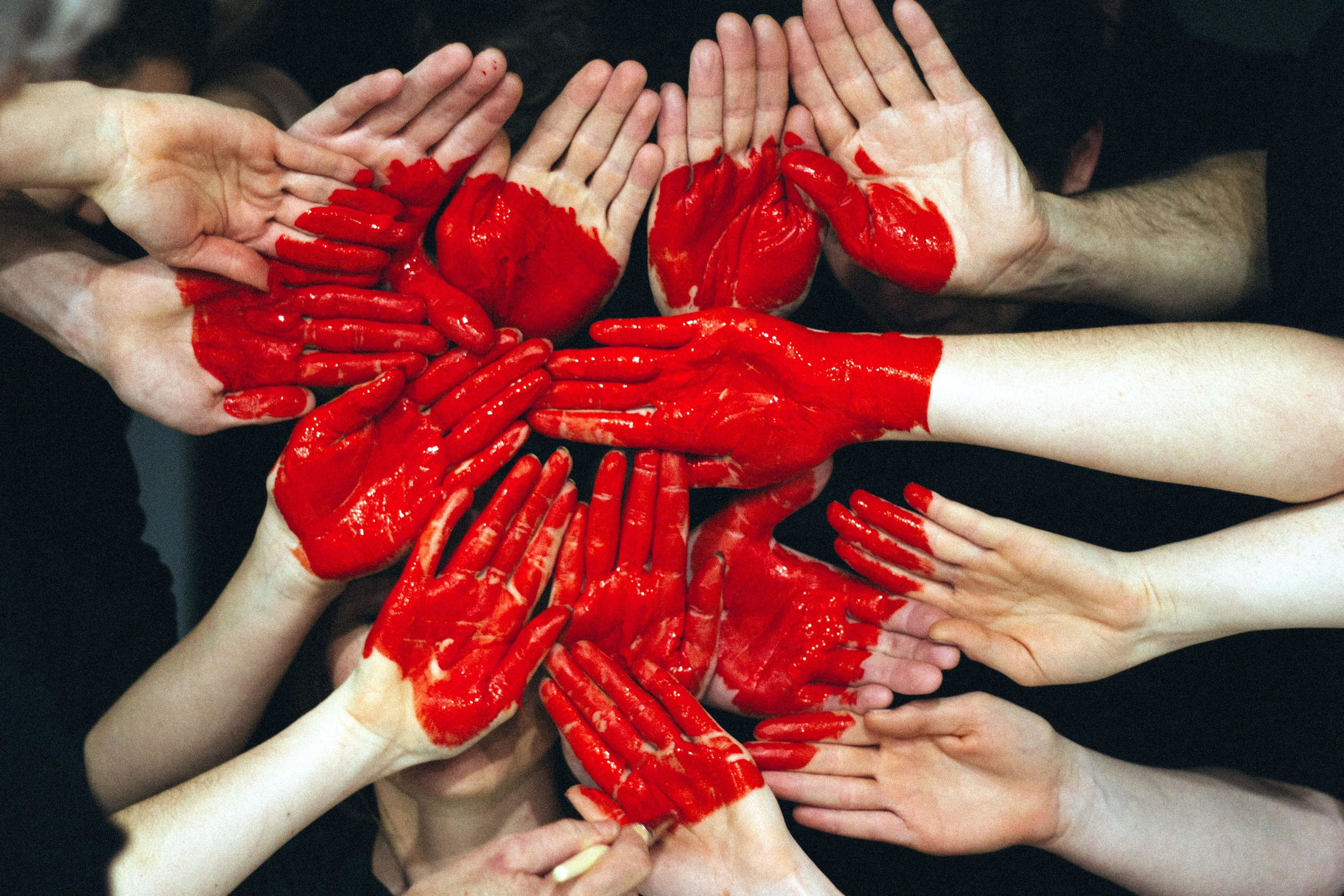 Hands all coming together with a painted red heart drawn on them
