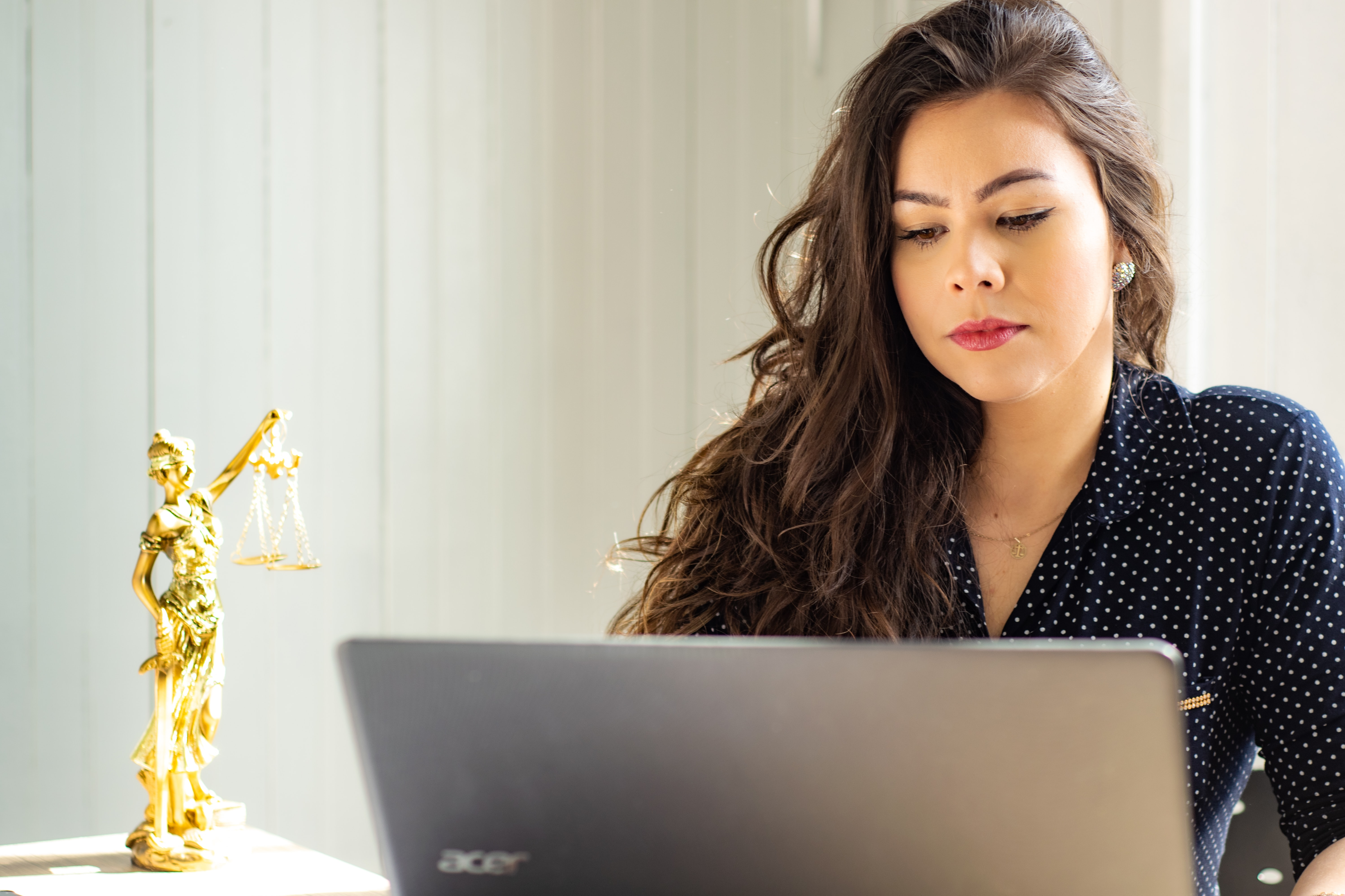 Women sat a a laptop with a gold ornament of justice on her desk