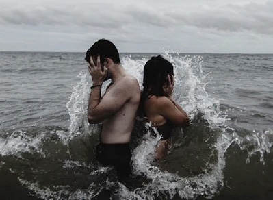 Man and woman head in hands, back to back in a choppy sea