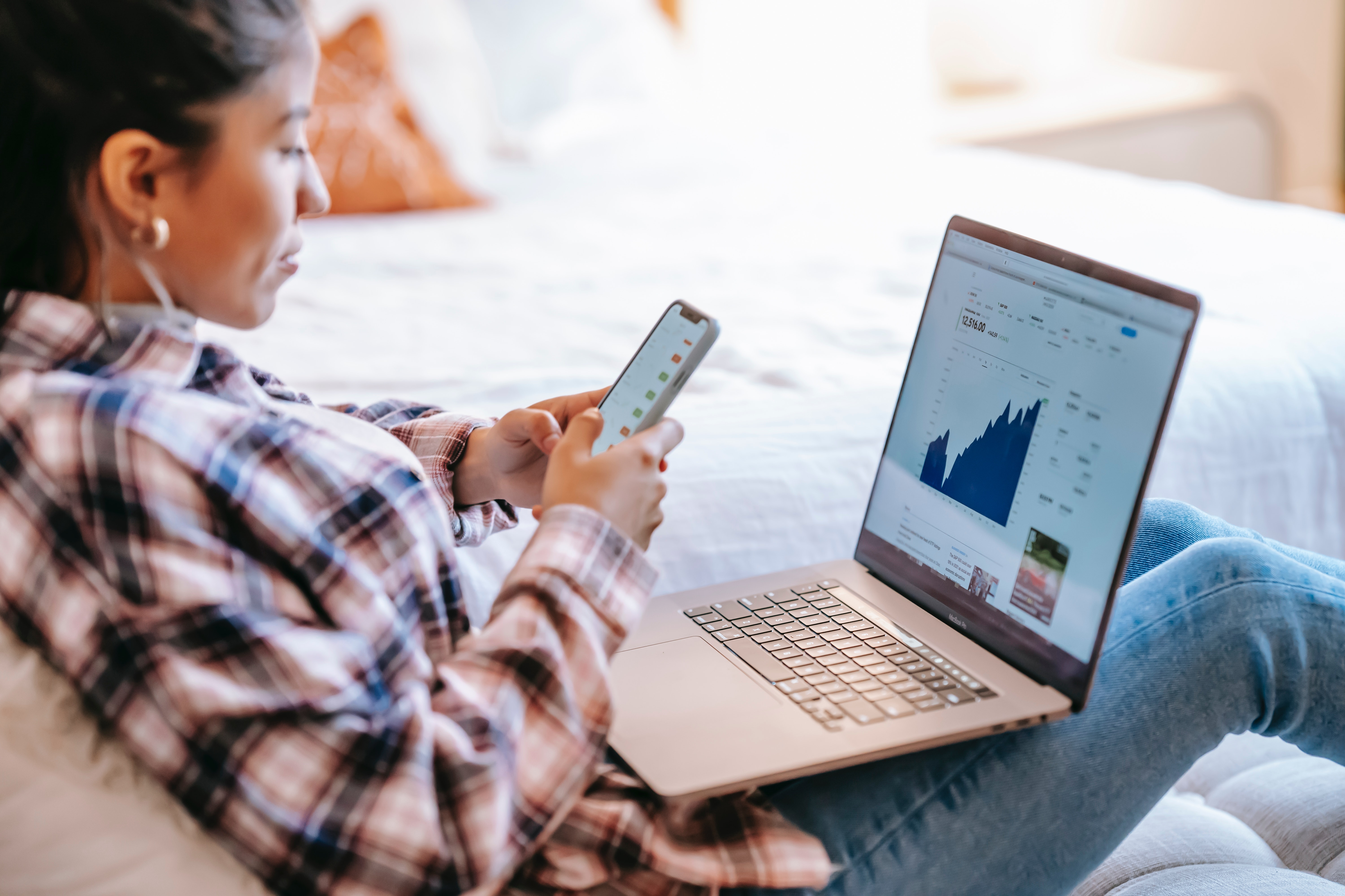 Woman sat on sofa looking at her finances on her phone and laptop