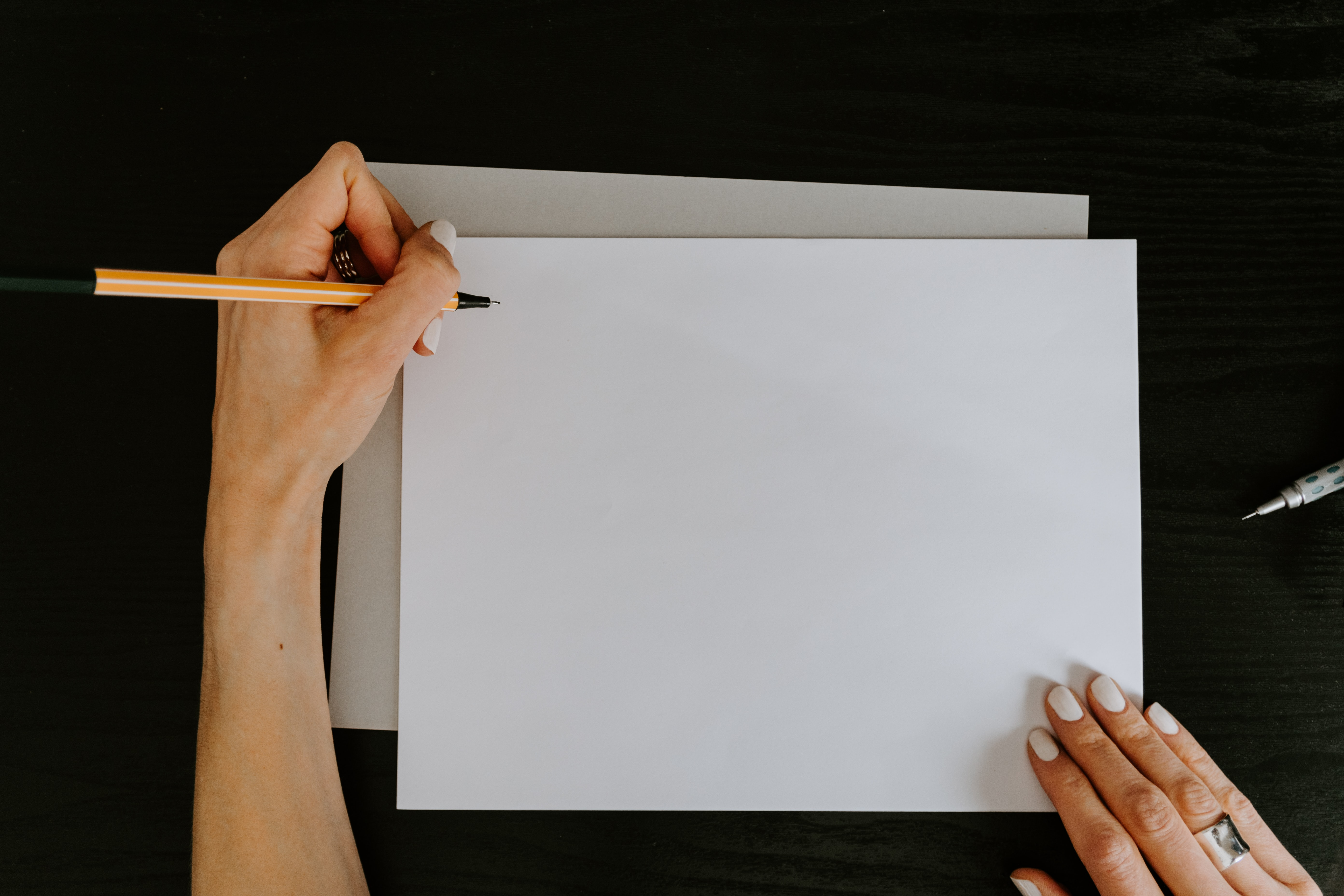 White blank sheet of paper with a woman holding a pencil
