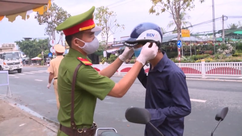 A policeman helping a rider fix their mask