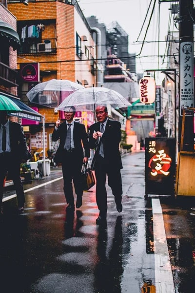Two Japanese people with briefcase and umbrella