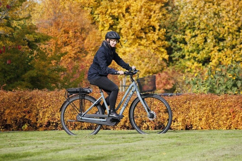 Madelene supporting sustainable transport riding her e-bike or electric bike in colorful autumn landscape.