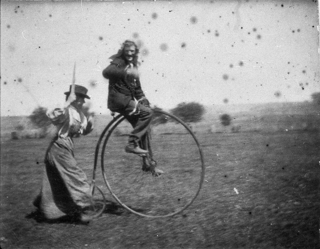 An old picture of a man using a bike with big front tire when it was just invented.