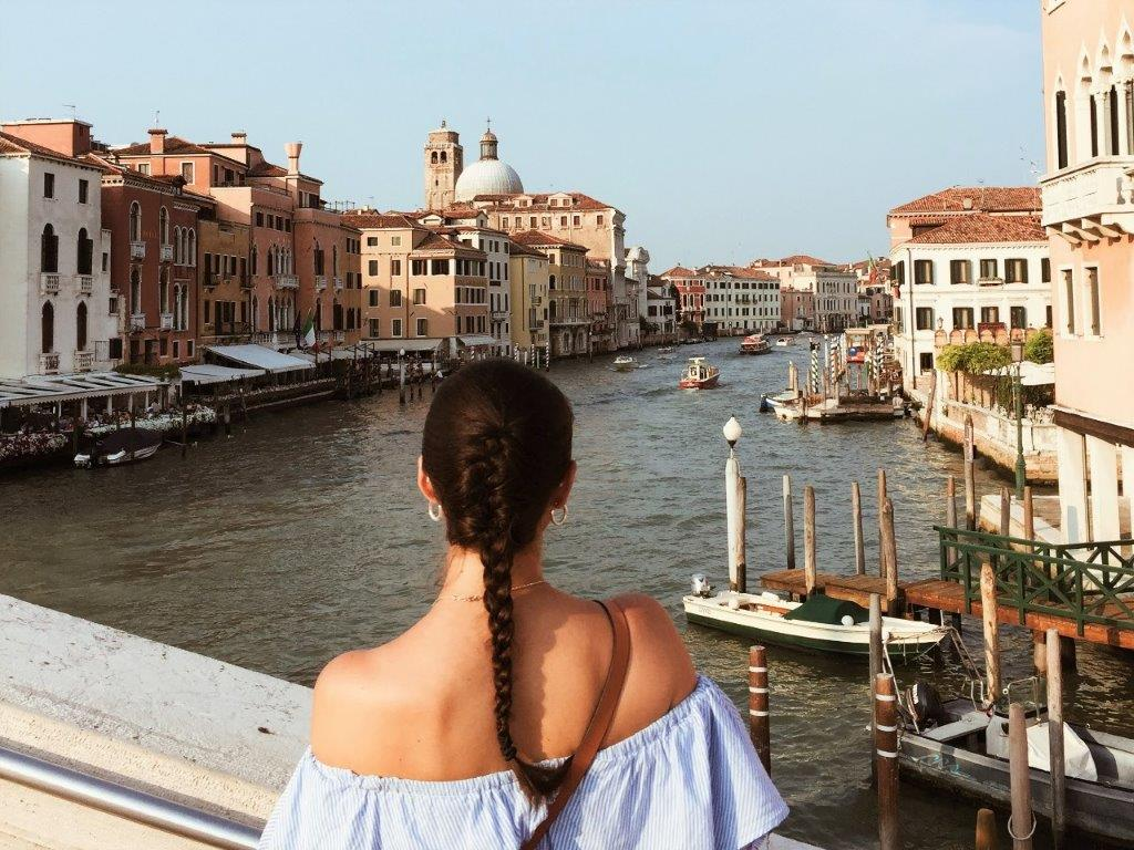 Woman looking over channel in Venice