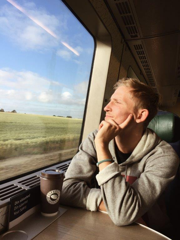 Man looking out of train window – enjoying sustainable traveling.