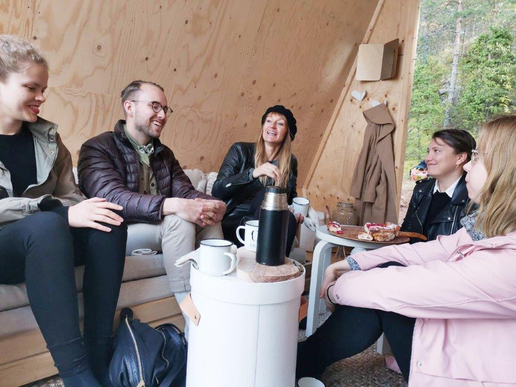 A group of people having a picnic inside the Nolla Cabin.