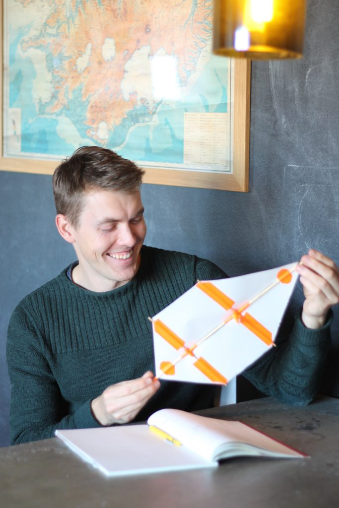 Sustainable engineering advocate holding a prototype of a wind turbine and smiling.