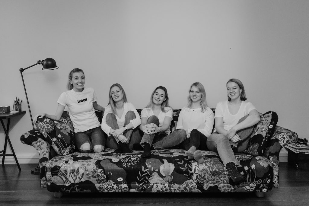 Spark Sustainability's climate-smart team laughing sitting on a sofa.