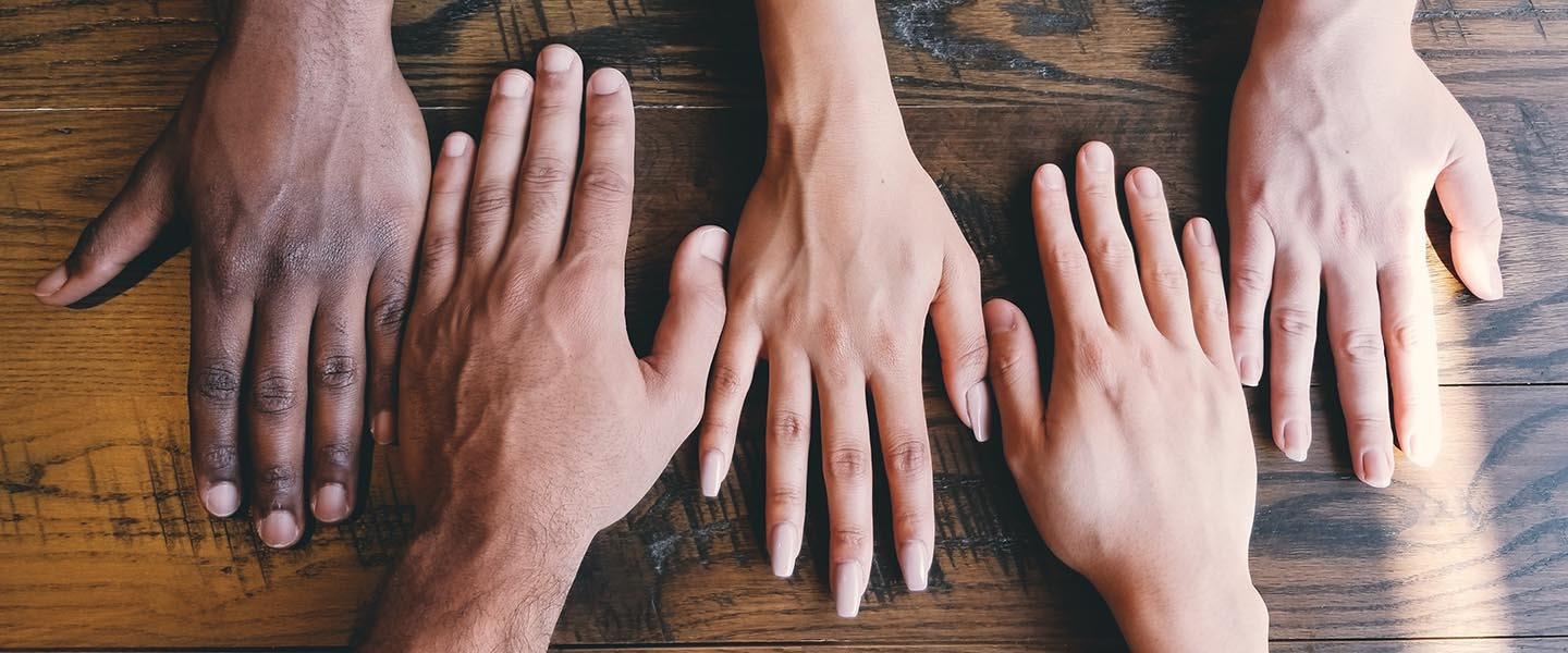 Five hands from a diverse group laying together on a table