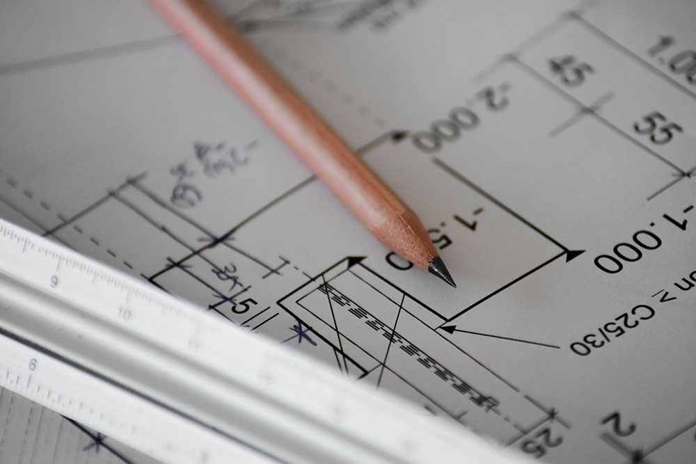 A pen and ruler on a paper floor plan.