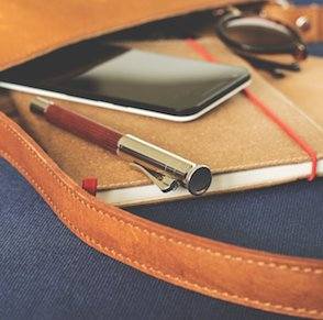 notebook pen phone sunglasses in bag lying on side