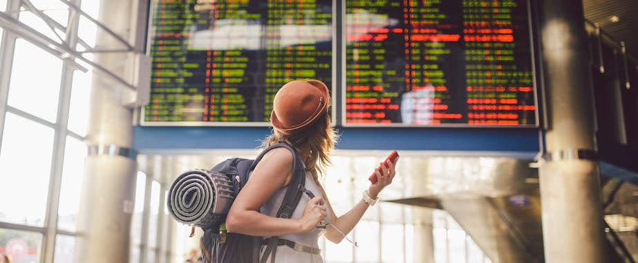 Backpacker checking flight schedules in airport