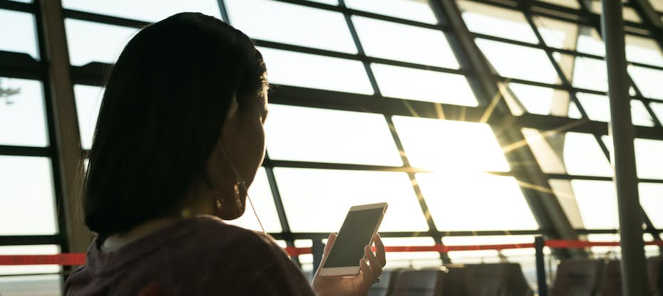 Woman checking phone in sunlit airport