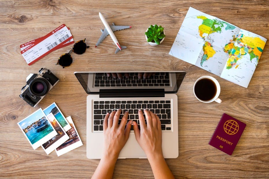 Planning a trip on laptop at desk with map, passport, photos, camera, etc.