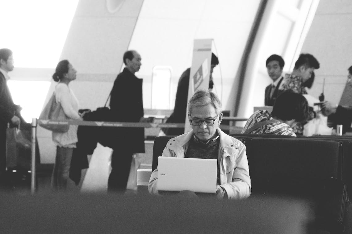 Black and white photo of man sitting in airport working on laptop