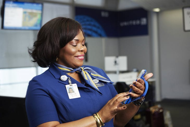 Smiling flight attendant checking airline app on phone