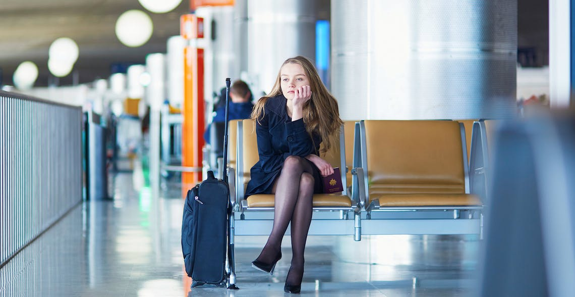 Young woman sitting alone in airport looking bored