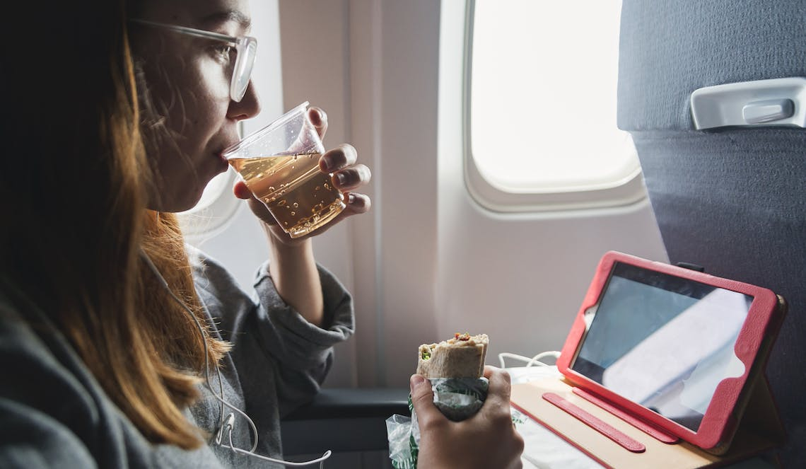 Young woman in window seat sipping beverage and holding sandwich while watching iPad