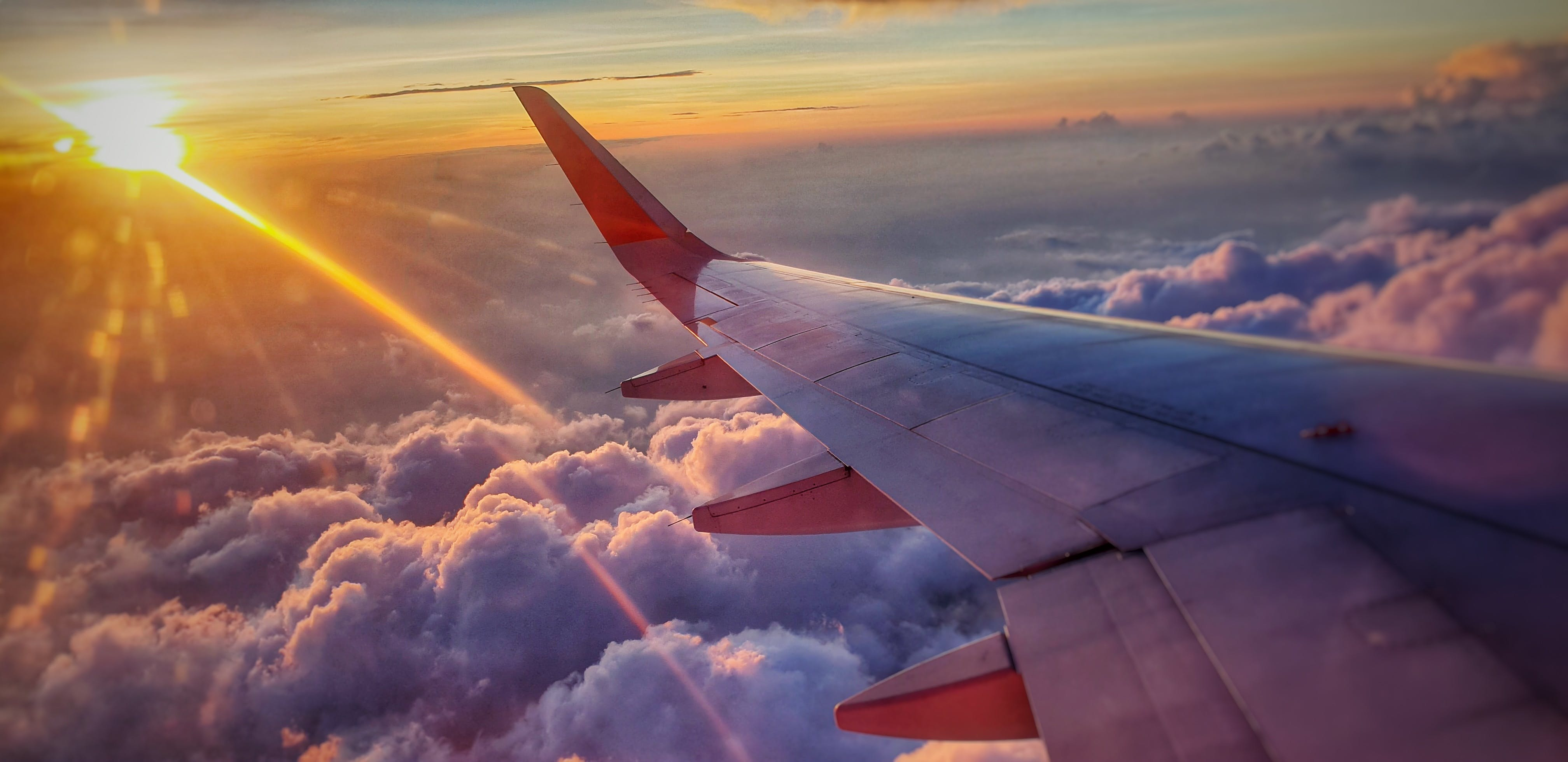 Airplane wing over clouds and sunset