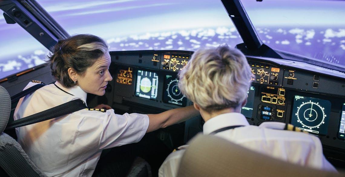 Pilot consulting copilot in cockpit while at cruising altitude