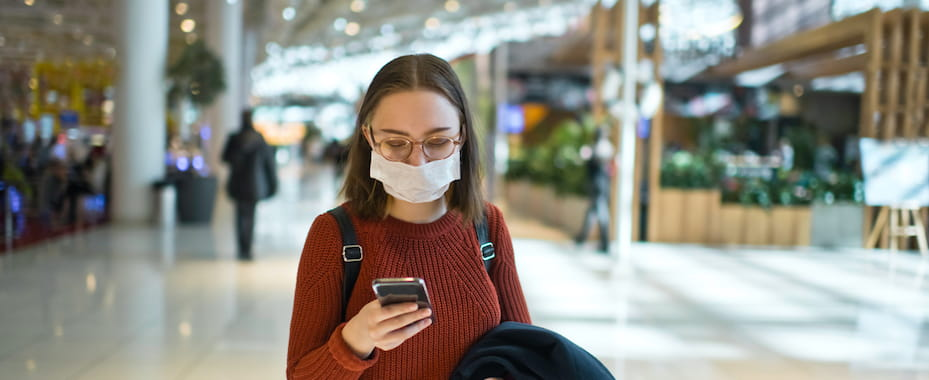 Woman in airport on mobile phone wearing protect face mask during Covid-19
