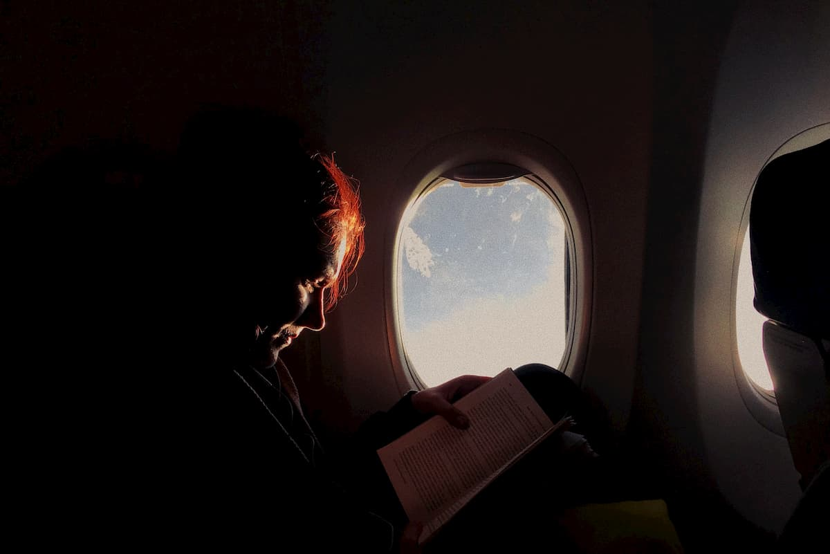 A person reading on a dark aircraft