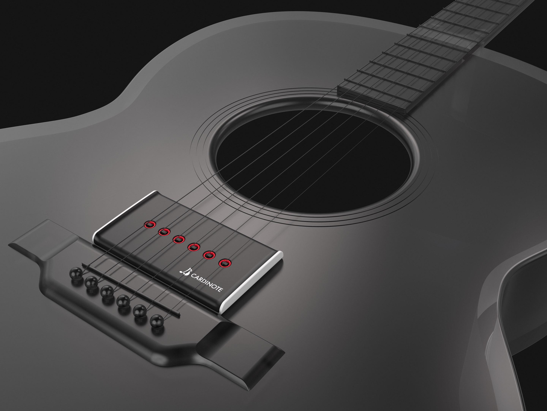 Cardinote Brio on black guitar and dark background with focus on bridge area.