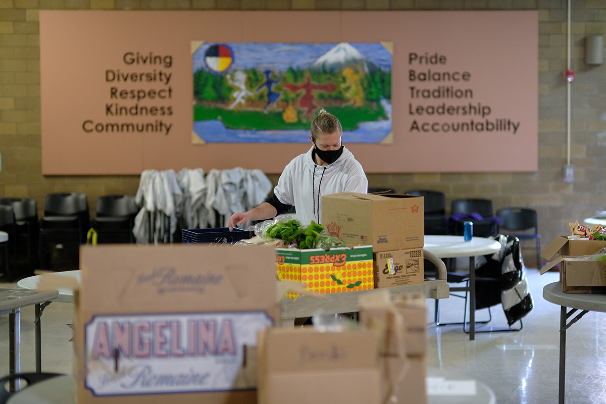 Volunteer packs boxes of food for community members at the Native American Youth and Family Center in Portland