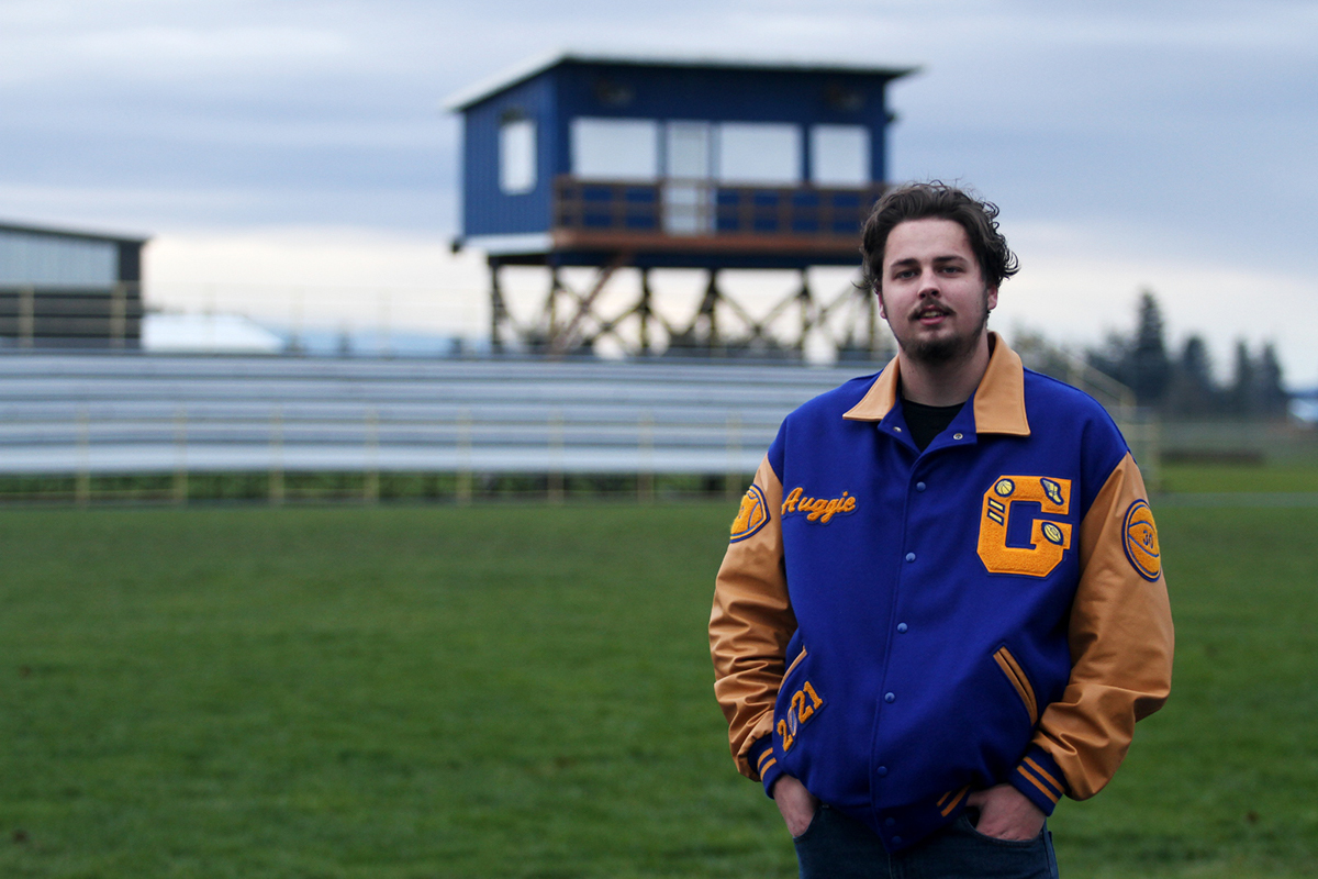 High school student in letter jacket stands in empty sports field
