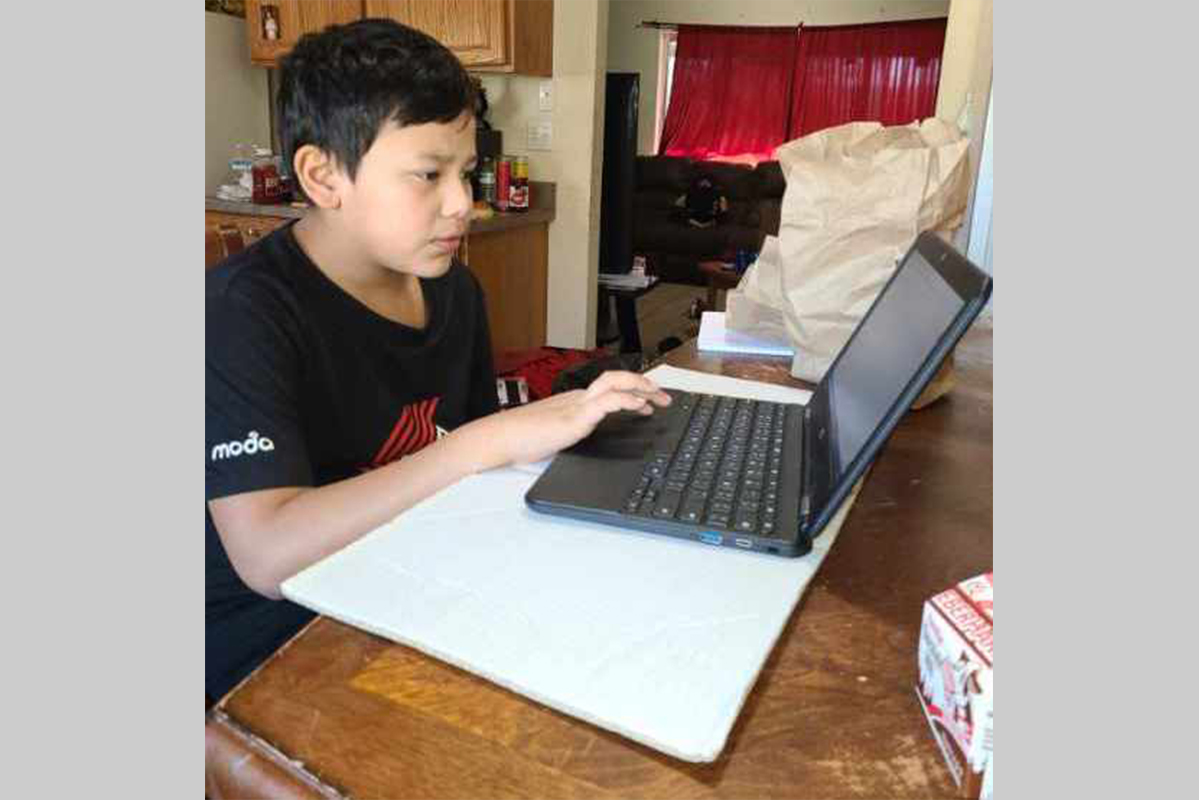 Student using a laptop to do school work from home.