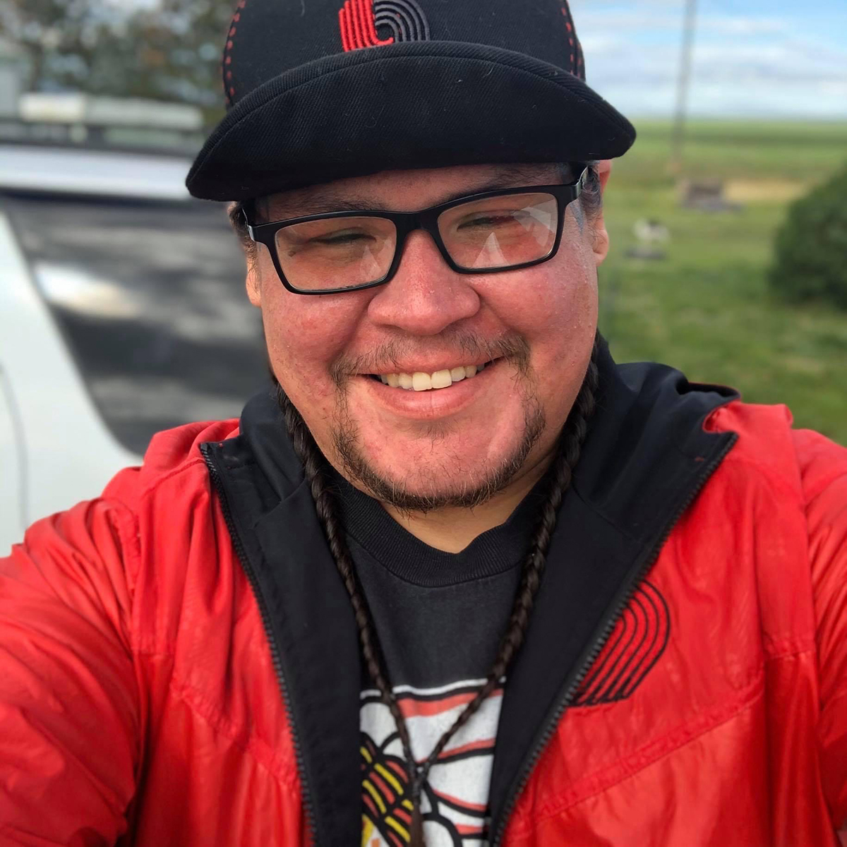 Closeup of smiling man with glasses and red jacket