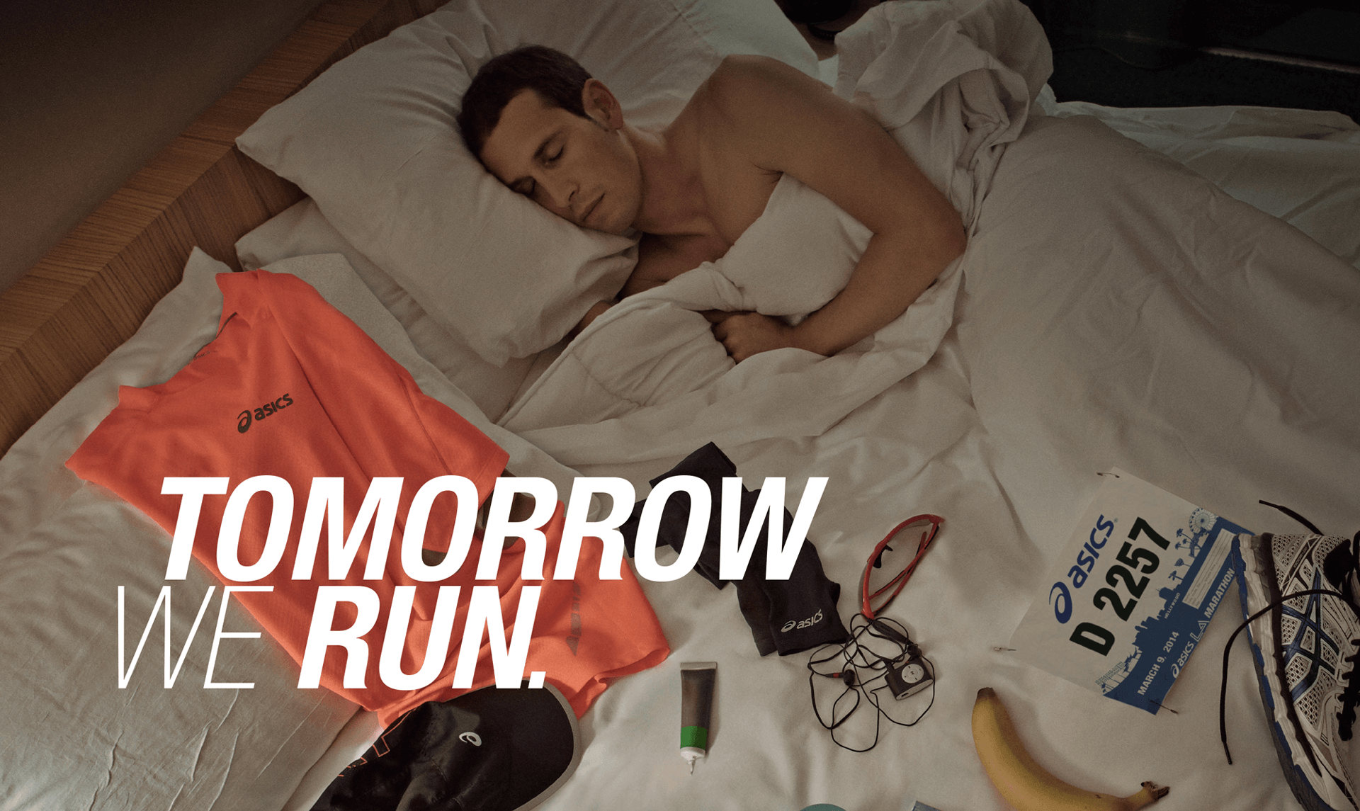 ASICS banner featuring male runner in bed with running gear