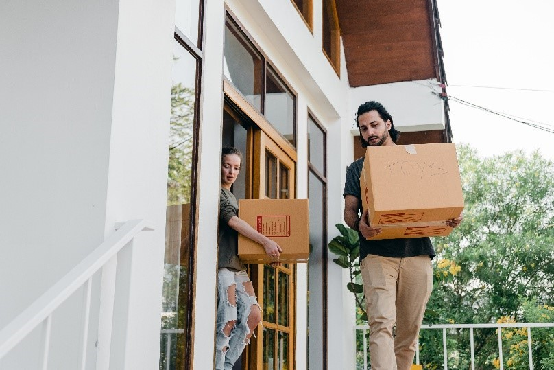 man and woman leaving house with boxes