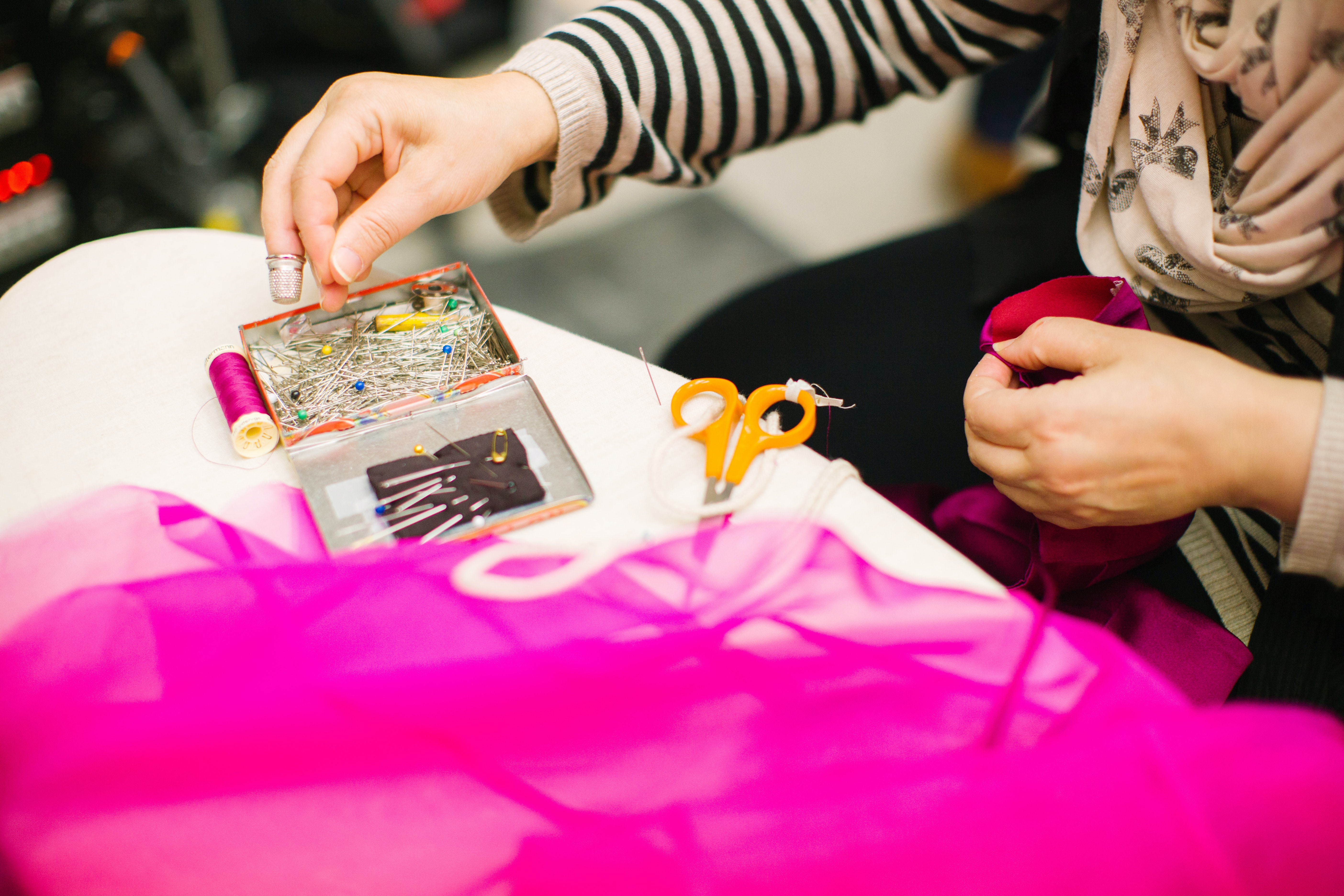 Visual aid for crafting e-commerce company case study - a crafter pins magenta tulle fabric for a sewing project.